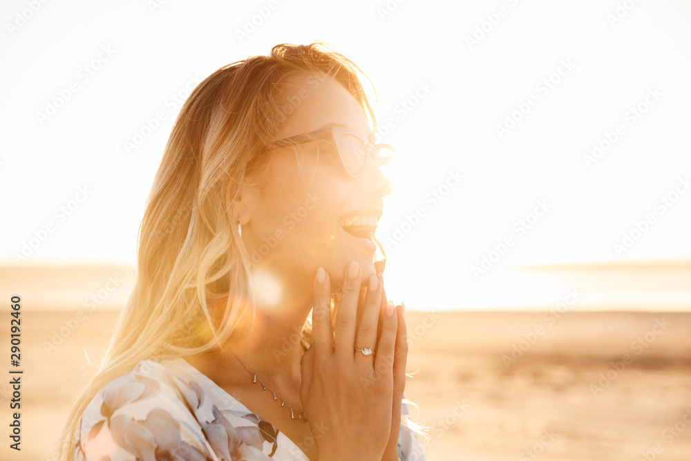 Fototapeta Photo of amazed young woman laughing and looking aside while walking on sunny beach