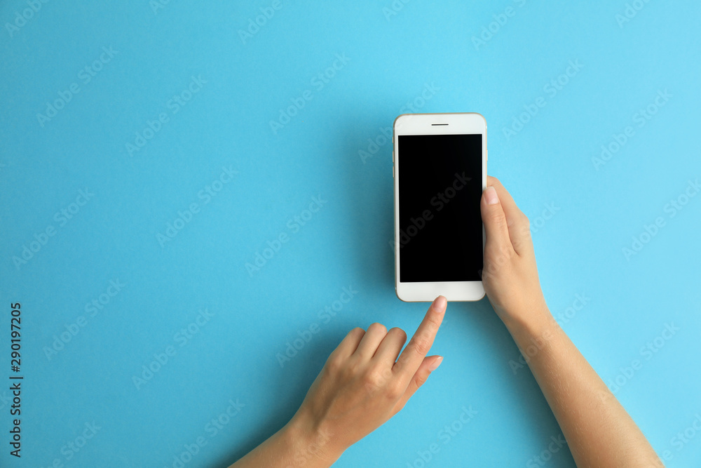 Fototapety, obrazy: Woman holding modern phone on blue background, top view. Space for text