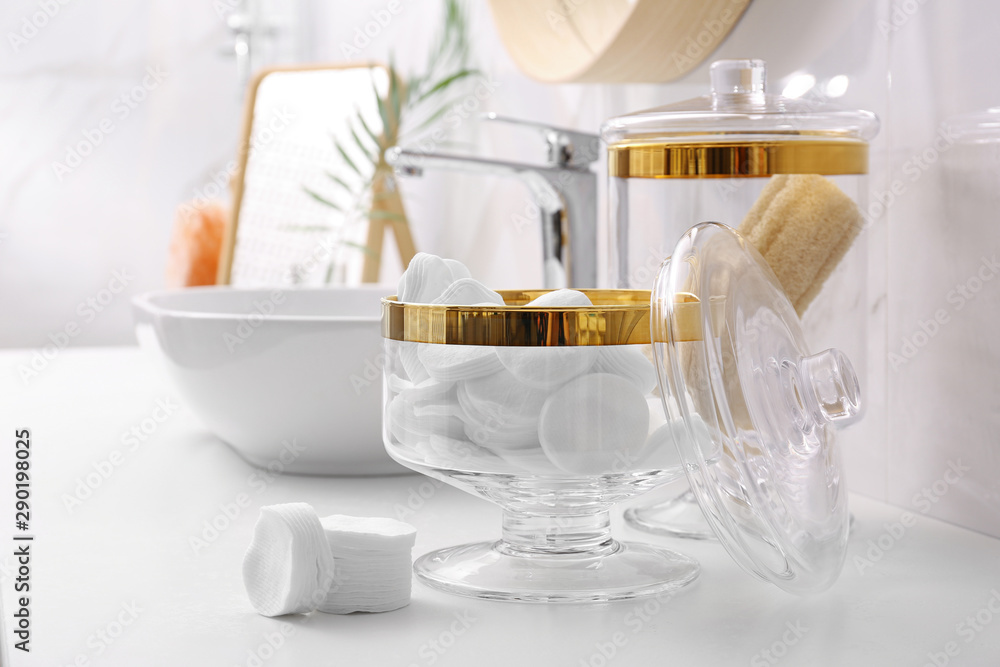 Fototapeta Glass jars with cotton pads and loofahs on table in bathroom