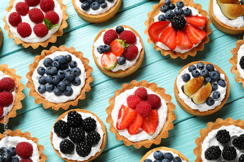 Fototapeta Many different berry tarts on blue wooden table, flat lay. Delicious pastries obraz