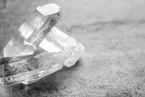Beautiful rock crystal gemstones on grey table, space for text