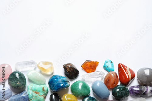 Different beautiful gemstones on white background, top view