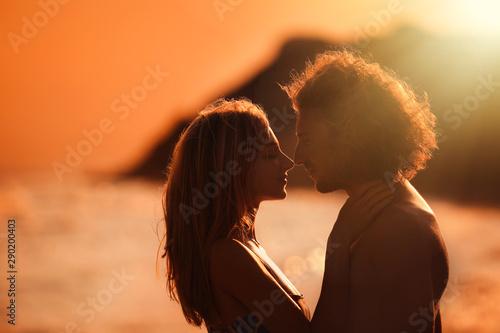 Fotografia  Young woman in bikini and her boyfriend on beach at sunset