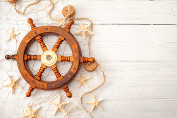 Summer vacation, sailing boat themed holiday house and marine exploration conceptual idea with vintage wooden helm used to navigate, fishing net and starfish isolated on white wood with copy space