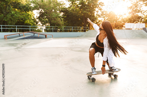 Poster Attraction parc Photo of active young woman riding skateboard in concrete park
