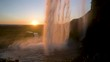 The sun slowly setting as the water falls over the cliffs at Seljalandsfoss waterfall.