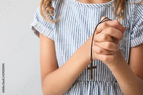 Praying little girl on light background, closeup Canvas Print