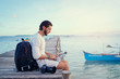 Work and travel. Young man with rucksack using laptop computer sitting on wooden fishing pier with beautiful tropical sea view.