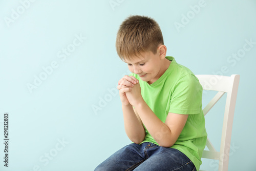 Praying little boy on color background Canvas Print
