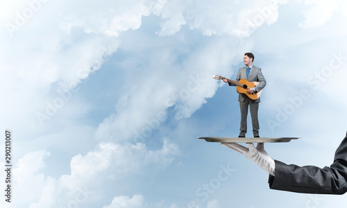 Businessman on metal tray playing acoustic guitar against blue sky background - 290213007