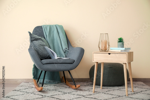 Obraz na plátně  Stylish armchair with table near light wall in room