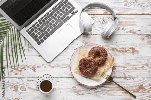 Foto op Canvas Brood Tasty donuts with laptop, headphones and cup of coffee on white wooden table