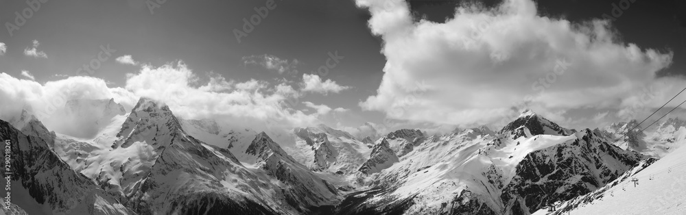 Fototapeta Black and white panorama of snowy sunlit mountains