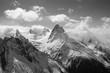 Leinwanddruck Bild Winter snowy sunlit mountains in clouds