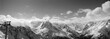 Leinwanddruck Bild Black and white panorama of snowy sunlit mountains in clouds