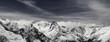 Leinwanddruck Bild Panorama of snowy winter mountain in sunlit clouds
