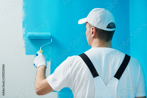 Photo sur Aluminium Graffiti collage Painter worker with roller painting wall surface into color