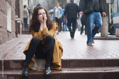 obraz PCV Sad young woman sitting outdoors in autumn on a rainy day.