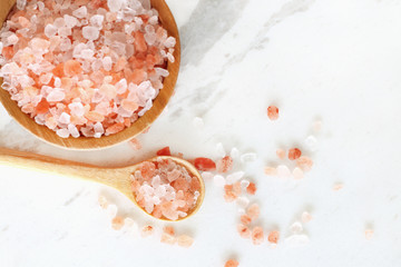 Fototapeta na wymiar top view of himalayan pink rock salt in wooden bowl and spoon on white marble table.