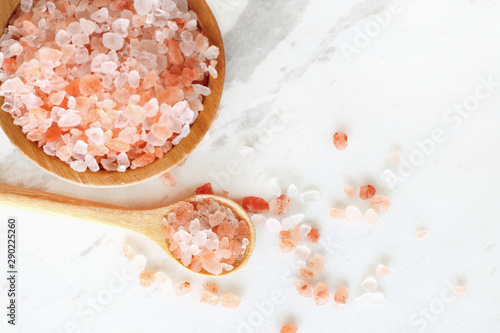 Fototapeta top view of himalayan pink rock salt in wooden bowl and spoon on white marble table.