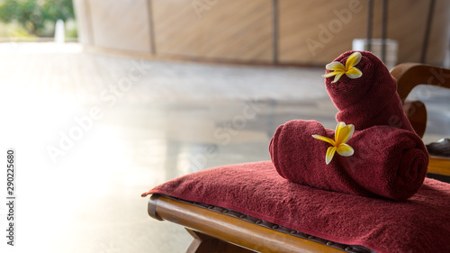 Towel and flowers on chair at resort spa - 290225680