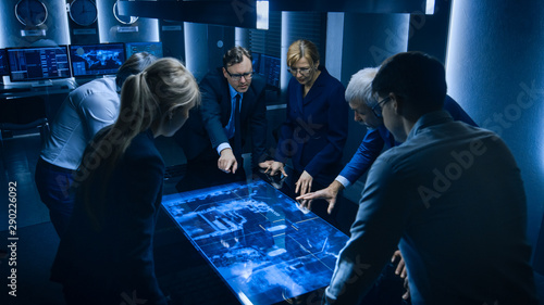 Cuadros en Lienzo Team of Government Intelligence / FBI Agents Standing Around Digital Touch Screen Table and Tracking Suspect Vehicle Using Satellite Surveillance in the Monitoring Room