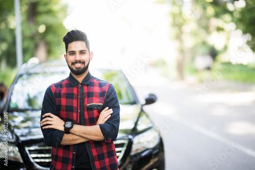 obraz dibond Young indian man standing near his car.