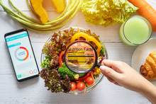 Nutritional Information Concept. Hand Use The Magnifying Glass To Zoom In To See The Details Of The Nutrition Facts From Food , Salad Bowl