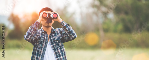Foto auf AluDibond Honig Man with binoculars telescope in forest looking destination as lost people or foreseeable future. People lifestyles and leisure activity concept. Nature and backpacker traveling jungle background