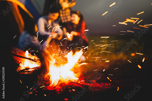 Foto auf AluDibond Schwarz Sparking bonfire with tourist people sit around bright bonfire near camping tent in forest in summer night background. Group of student at outdoor fire fuel. Travel activity and long vacation weekend