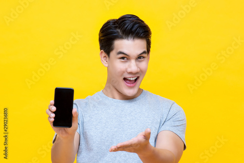 Fotomural  Smiled young good looking Asian guy showing smartphone