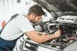 young smiling handsome mechanic in uniform fixing motor problems in car bonnet working in service center