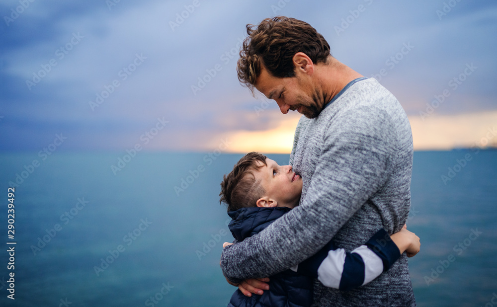Fototapeta Father with small son on a walk outdoors standing on beach at dusk.