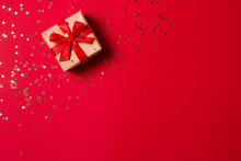 Christmas Composition Greeting Card. Gift From Craft Paper On A Red Background With A Gold Star Confetti. Top View, Flat Lay.