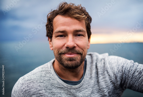 Obraz A portrait of handsome man standing outdoors, looking at camera. - fototapety do salonu
