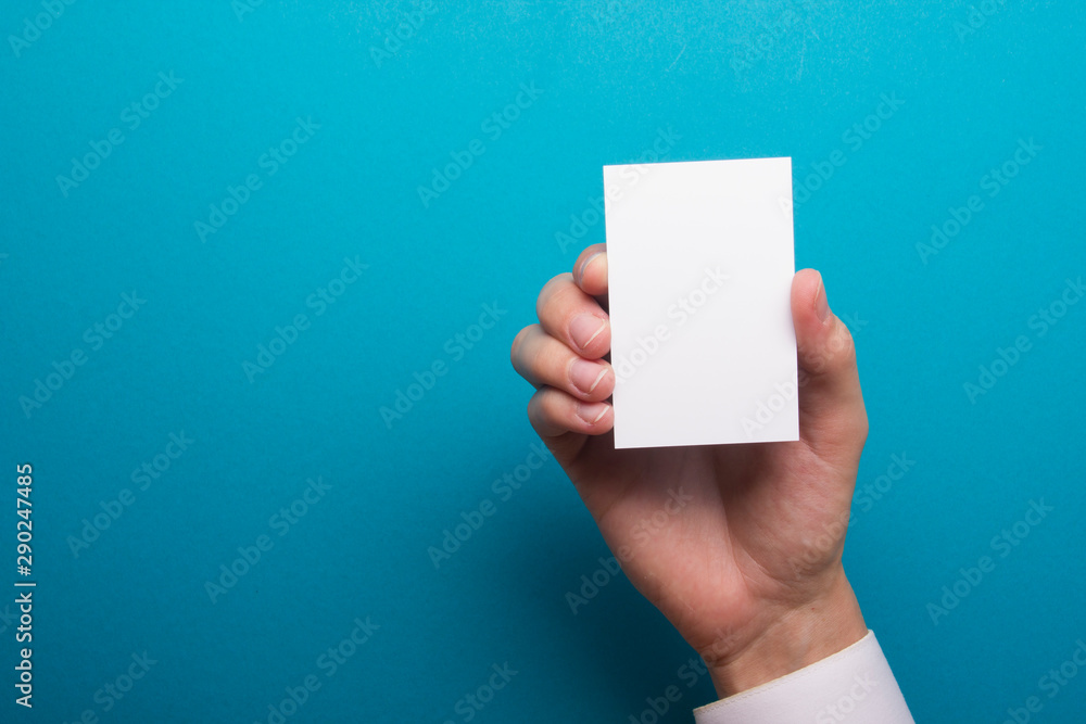 Fototapeta Hand holding business card blank on abstract background