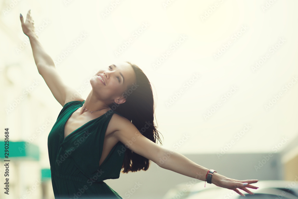 Fototapeta Young pretty likable cheerful woman posing summer city outdoor. Beautiful self-confident girl dressed in emerald-colored jumpsuit with long brown hair dancing enjoing life.