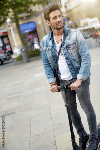 Trendy guy in town using electric scooter Slika na platnu