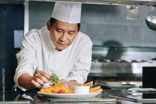 Fototapeta Asian mature chef decorating his dish with greens before serving in the kitchen obraz
