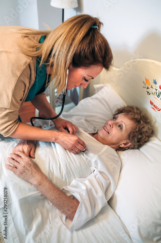 Female caregiver auscultating senior woman at home Canvas Print