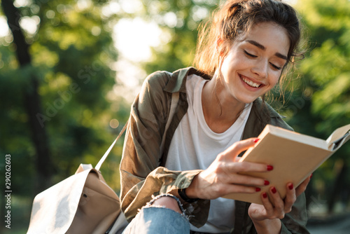 Image of attractive woman smiling and reading book in green park