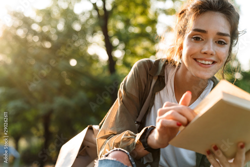 Image of beautiful woman smiling and reading book in green park