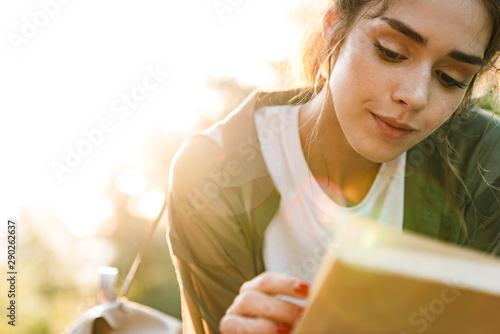 Image of lovely woman reading book while walking in green park Canvas-taulu