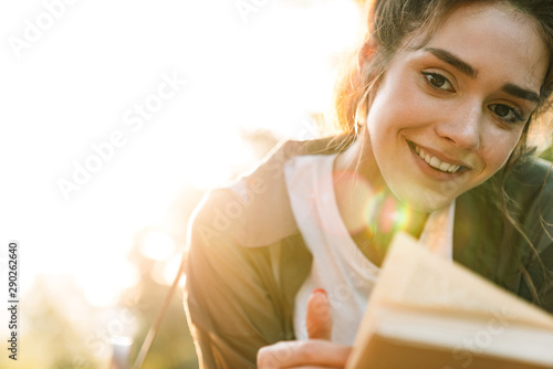 Foto auf Leinwand Lineale Wachstum Image of joyful woman smiling and reading book in green park