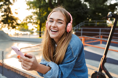 Positive young teenage girl outside in park holding mobile phone. - 290269086