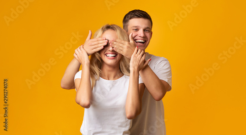 Fototapeta  Hide and seek. Guy standing behind girlfriend closing her eyes