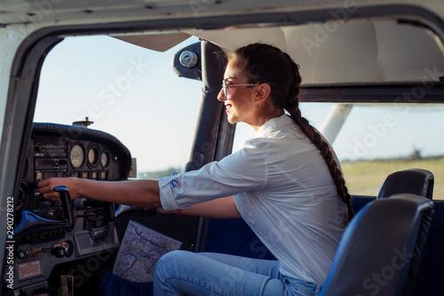 Female pilot preparing for a flight in a light aircraft Fototapeta