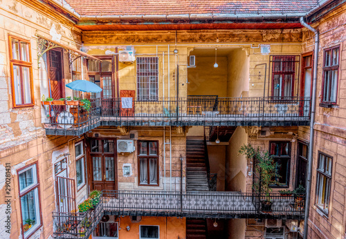 Fotografie, Obraz Budapest, Hungary -August 29, 2019: Staircase, forged railing and arched door in an old apartment building in Budapest, Hungary