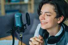 Emotional Teenage Kid Is Speaking In Microphone In Studio Recording Podcast Gesturing Expressing Opining For Online Blog. People And Modern Lifestyle Concept.