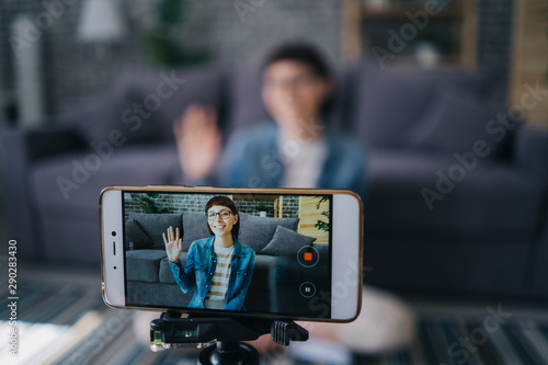 Fotomural Joyful girl recording video with smartphone camera talking waving hand at home, focus on mobile screen